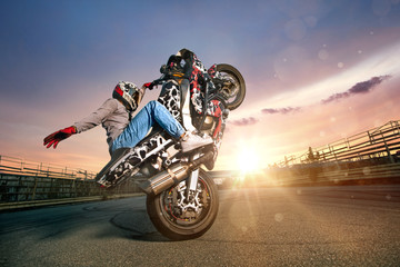 Moto rider making a stunt on his motorbike. Biker doing a difficult and dangerous stunt. Wall mural