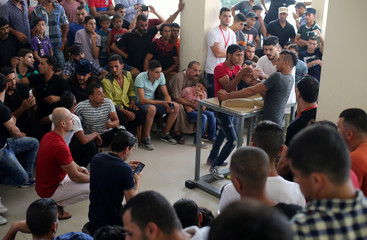 People watch as Palestinians participate in a local arm-wrestling competition in Deir al-Balah in the central Gaza Strip