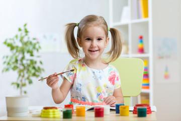 Smiling child girl painting in kindergarten
