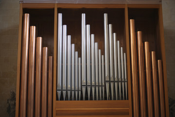 Copper and silver organ pipes in the Catholic basilica. Lecce, Italy.