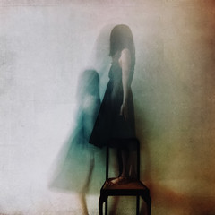 Ghostly image of unrecognisable woman standing on a chair (heavily textured)