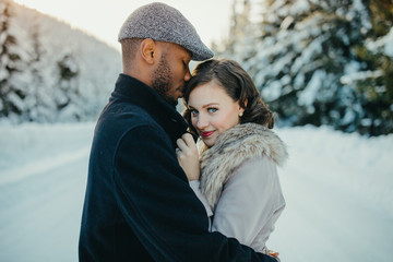 Young mixed couple embrace in love on snow covered winter lake