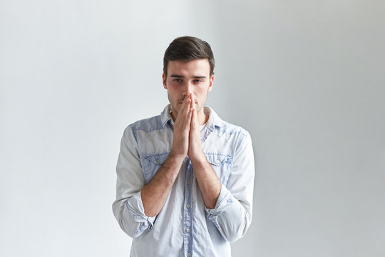Isolated portrait of thoughtful hopeful young man in denim shirt praying, holding clasped hands at his face and having worried look. Frustrated male facing problem, hoping for the best. Body language