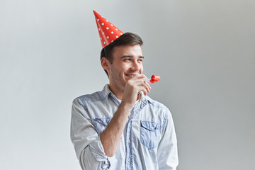 Handsome cheerful young man with dimpled smile having fun on party wearing blue denim shirt and red holiday hat, blowing iparty horn and laughing. People, joy, birthday and celebration concept