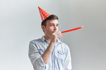 Studio shot of unshaven young Caucasian male blowing whistle while celebrating his friend's birthday, having relaxed and cheerful expression on his face. Happy guy posing wih red party horn
