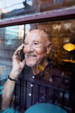 Elderly man looking through the window talking on phone.