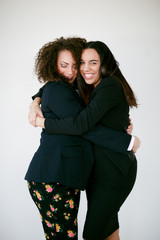 Two young women embrace in a hug