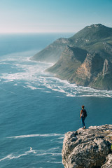 Hiker on a rocky outcrop overlooking an expansive scenic sea view