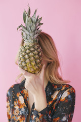 Woman hiding face behind pineapple
