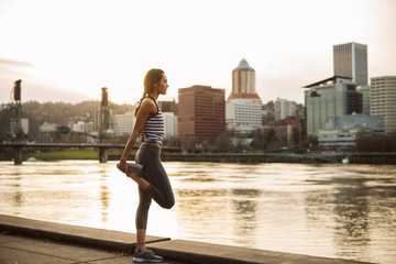Fit young woman exercising by the city waterfront at dusk