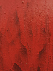 Bright red paint covering graffiti on wall, close up