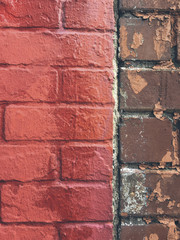 Vivid red paint covering graffiti on brick wall, close up