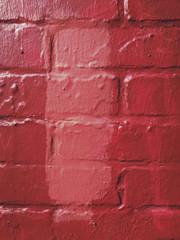 Vivid red paint covering graffiti on brick wall, close up