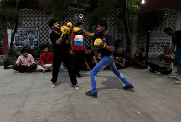 Men train during a boxing lesson at a boxing club in Rawalpindi