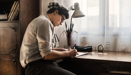 Young stylish man drawing new tattoo sketch on paper in vintage studio.