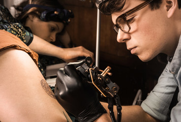 Tattoo session  in retro vintage tattoo studio