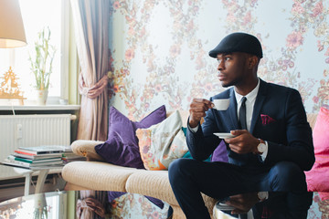 Stylish Young Black Man Sitting in Bright Living Room and Drinking Espresso