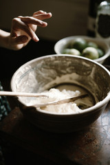 Hand finishes mixing icing in a ceramic bowl