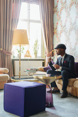 Profile of Handsome Young Black Man Sitting in Bright Living Room and Drinking Espresso