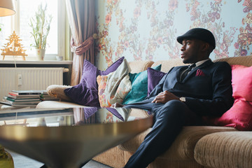 Elegantly Dressed Young Black Man Sitting on Sofa in Ornate Living Room