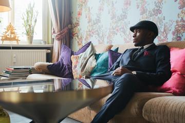 Elegantly Dressed Young Black Man Sitting on Sofa in Ornate Living Room