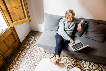 Blonde woman sitting on couch using laptop.