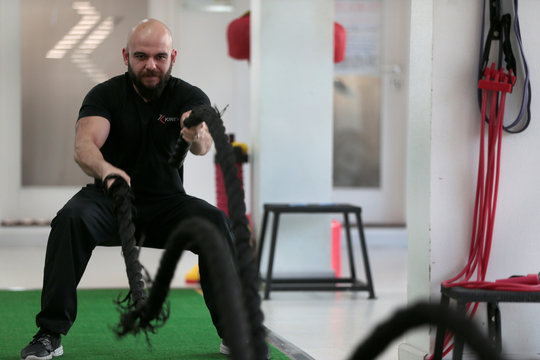 An trainer shows his client the technique to battle ropes during a cross fit training at a gym in Islamabad