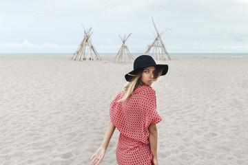 Fashionable Bohemian Woman In Hat On Sandy Beach
