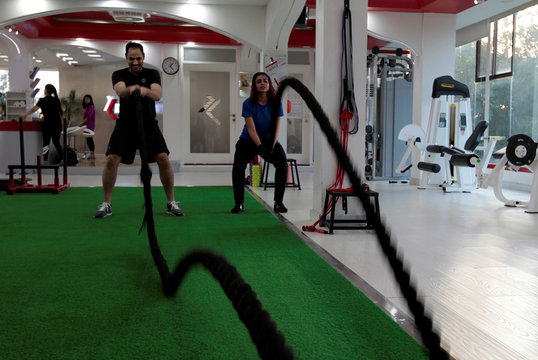 A man and woman train using battle ropes during a cross fit training at a gym in Islamabad