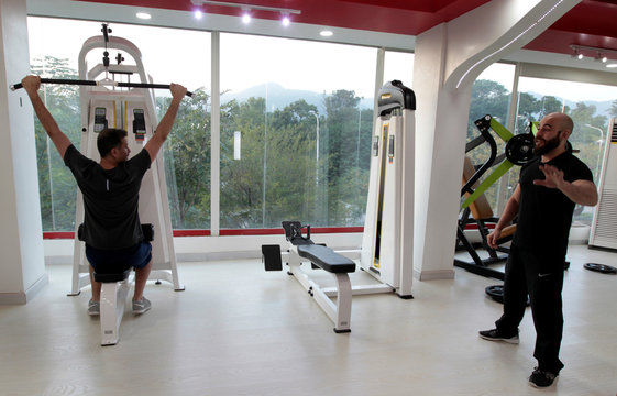An trainer speaks with his client during a cross fit training at a gym in Islamabad