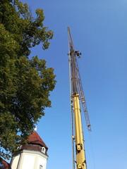 Gelber Baukran vor blauem Himmel auf einer Baustelle in Oerlinghausen bei Bielefeld im Teutoburger Wald in Ostwestfalen-Lippe