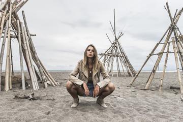 Woman Wearing Leather Jacket Sitting On Sandy Beach