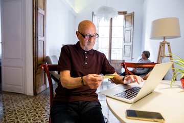 Elderly man shopping online on his laptop at home.