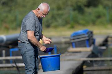 old man holding bucket at fish farm