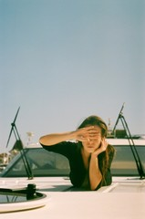 A film portrait of young beautiful woman closing her eyes on the yacht