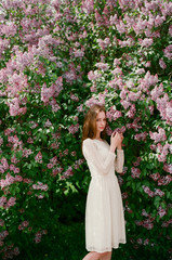 Young woman posing among lilac in blossom