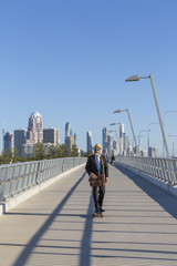 Alternative businessman skateboarding across bridge with tall buildings in background