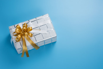 Silver white gift box with gold and white ribbon bow on blue background