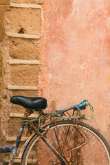 A rusty bicycle leant on a sandstone wall in Morocco