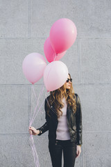 Young woman holding colorful pink balloons