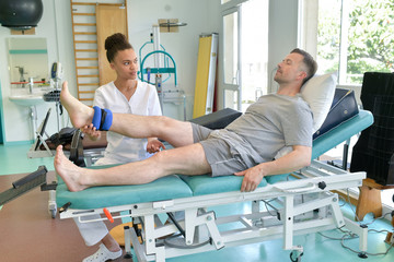 male patient sitting on table during physical therapy