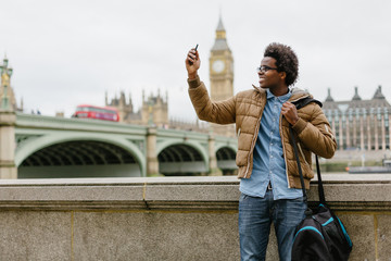 Young Black Commuter with Mobile Phone in London