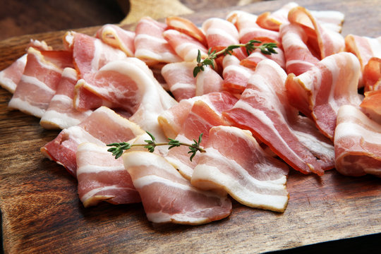 Raw sliced bacon with thyme leaves ready for cooking.