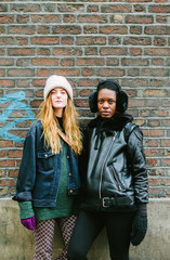 Two women in front of a brick wall in winter