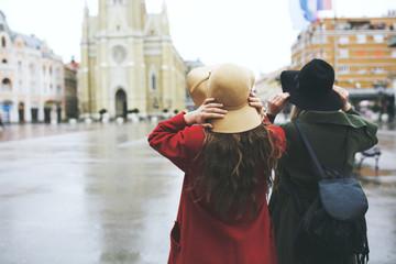 Two fashionable female friends walking on street