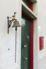 Old iron duck stands on top of bell ring in front of door