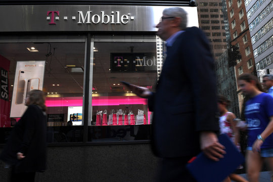 A pedestrian hold his smart phone as he passes a T-Mobile retail store in New York City