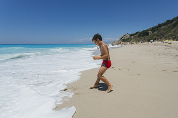 Boy playing on the beach.