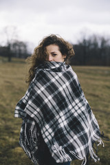 Portrait of young woman wearing a poncho, outdoors