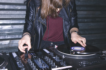 Young female DJ playing music at DJ desk